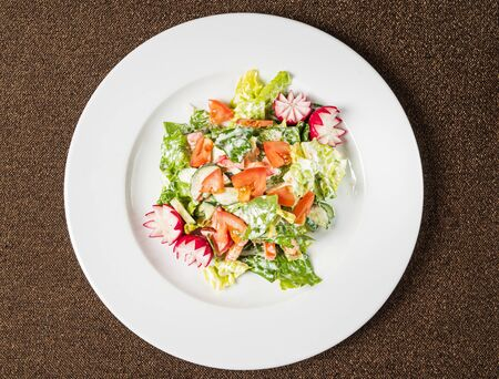 salad with fresh vegetables on the white plate