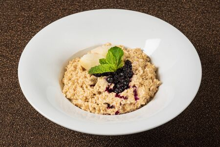 Bowl of oatmeal porridge with berry sauce