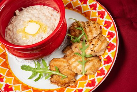Bowl with prepared oatmeal with butter and chicken fillet Imagens