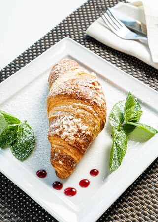 fresh croissant and cappuccino on table