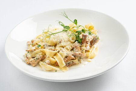 pasta with chanterelles on white plate Фото со стока