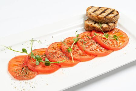 tomato carpaccio with toasts on white plate