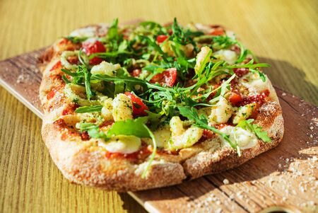 fresh pizza with calamari and arugula
