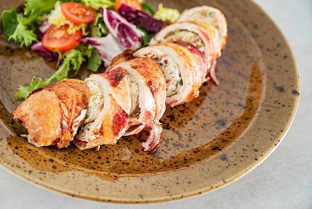 stuffed chicken wiht bacon and salad Imagens