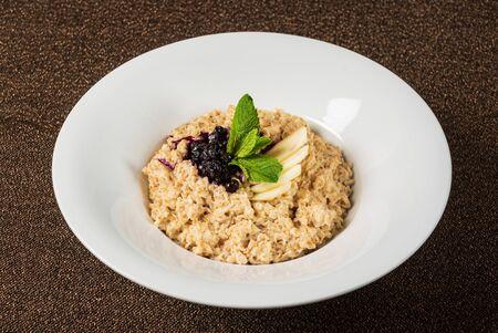 Bowl of oatmeal porridge with berry sauce