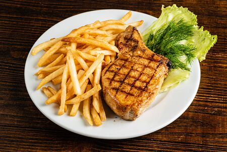 steak with french fries on the wooden background
