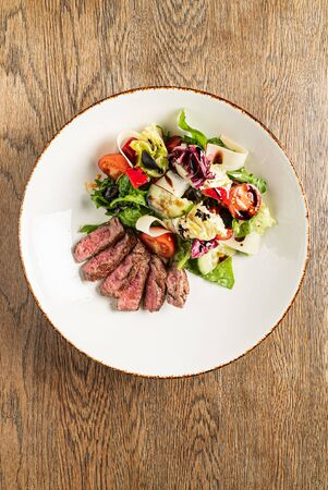 salad with beef on the wooden background