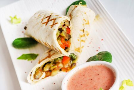 Tortilla wrap with sauce on marble plate