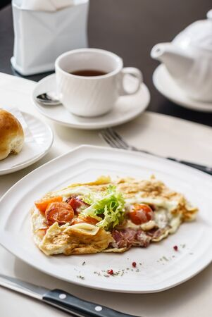Omelet with vegetables and ham on white plate