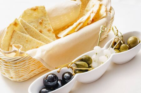 Pita chips with olives on white