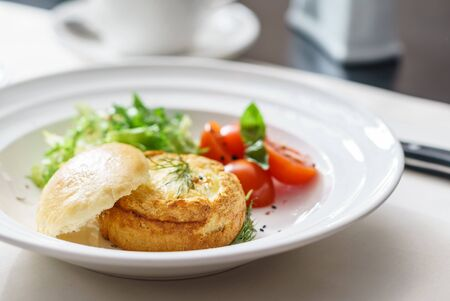 Eggs Benedict with fresh salad on white plate