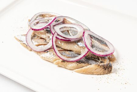 herring with red onion on the white plate