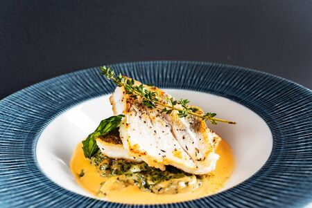 Fried fish fillet. Cod with sauce and herbs