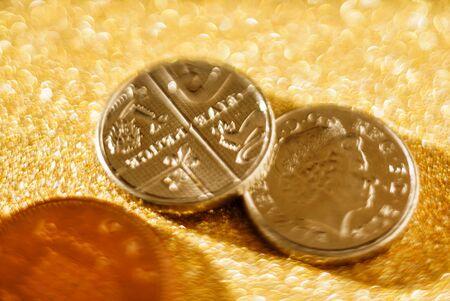 British Pound coins on the golden background