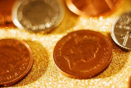 British Pound coins on the golden background Archivio Fotografico