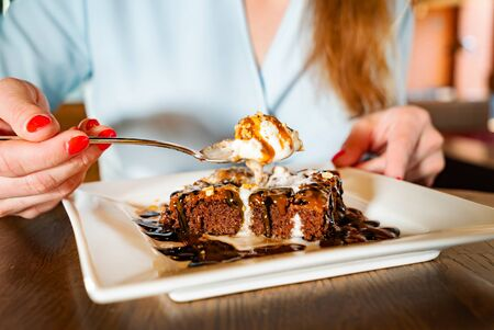woman eating brownie with ice cream