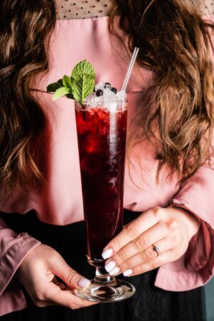 woman with fresh blueberries mocktail