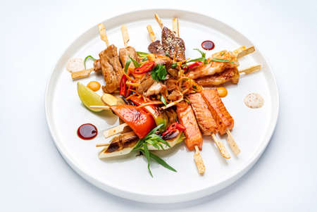 meat and fish kebabs on white plate