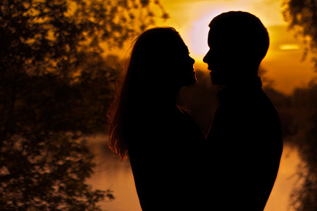 Loving couple in the park. / Couple in hug watching sunrise togethe 스톡 콘텐츠