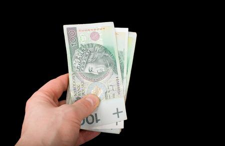 Polish money in hand on black background. Range of Polish banknotes in hand. 100 PLN