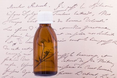 Bottle of essential oil, body care. Natural skincare, top view. Naural Remedies - Bottles and vintage text.