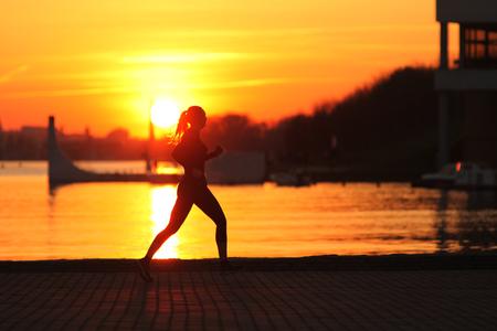 Running woman. Runner is jogging on sunrise. Female fitness.  Running Girl In The Beach At Sunset