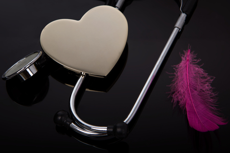 Stethoscope and heart - Healthcare. Black background. Risk of heart attack, hospital. Stock Photo