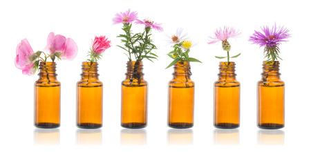 Bouteille d'huile essentielle aux herbes. Groupe de bouteilles brunes avec des fleurs des champs.