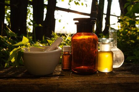 Phytotherapy - nettle in a mortar in the forrest. Bottles with herbal extracts on wood. Zdjęcie Seryjne