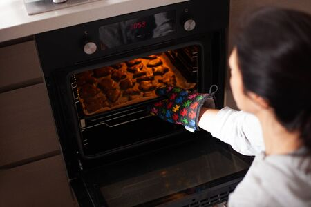 Woman pulls gingerbread out of the oven. Traditional Christmas gingerbread baking.