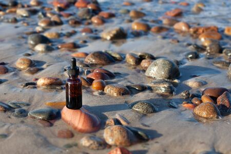 Homeopathy - a medicine bottle on the beach. Naturotherapy - herbal treatment, pebbles.