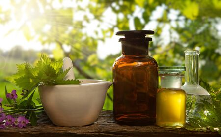 Herbs from the garden and various types of oils for massage and aromatherapy. Tincture bottles or mixtures and healthy herbs, a handful of medicinal herbs in a mortar on a table outside.
