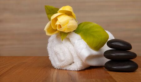 Roll of white towels on table, yellow flower -  with copy space. Spa background stock photo - baners.