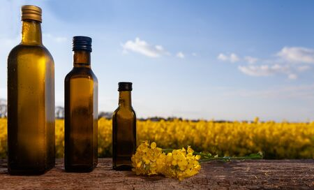 Rapeseed oil (rapeseed) and rapeseed flowers on a wooden board. Rapeseed field outside - a few bottles with oil.