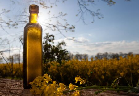 Tapeseed oil in bottles on white wooden table on background flowering rape field. Fresh rapeseed oil in a bottle.