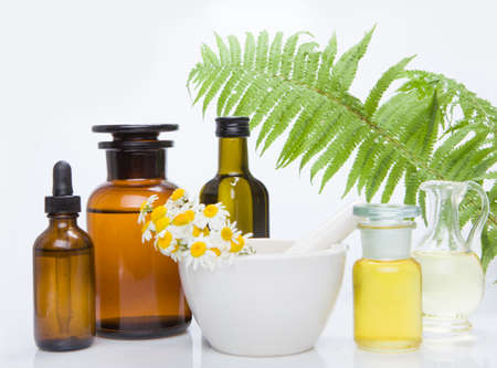 Healing herbs with mortar and bottle of essential oil.