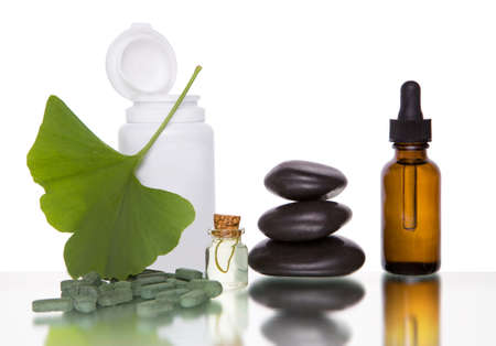 Alternative medicine - ginkgo leaves and tablets na bottle. Isolated over white background