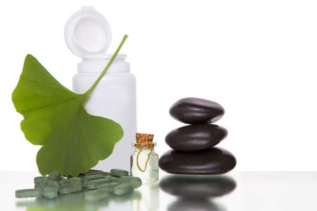 Pills with extract from the ginkgo in bottle and green leaves isolated on a white background.