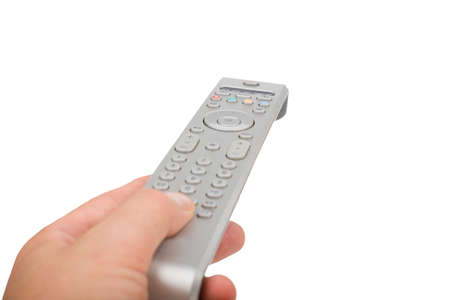 TV silver remote control in hand isolated closeup. Male hand changing channel with remote control isolated.