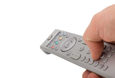 Hand pressing silver remote control isolated on white background. TV silver remote control in hand isolated closeup.