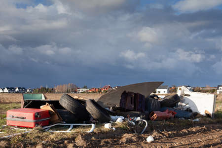 Poznan, Poland - April 02, 2021: Illegal dump near the country sand road in the country. Cloudy sky