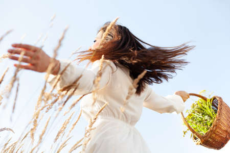 Dancing woman with wicker baskets in the meadow. Collection of herbs in the basket. Positive scenery. Archivio Fotografico