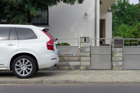 White car at the gate of a modern residential building. Archivio Fotografico
