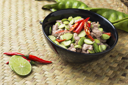 south asians: Pad Sa tor Ka pi Moo Fired Parkia speciosa beans with Shrimp paste and pork traditional Thai food from South of Thailand. beautiful thai food cuisine on  natural wicker mat background