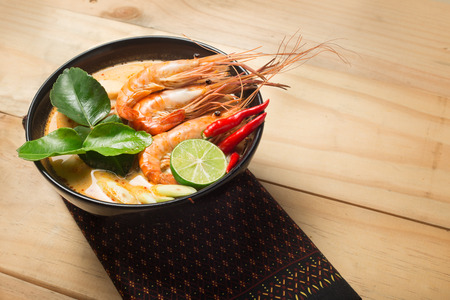 Tom Yum Goong spicy soup traditional thai food cuisine in Thailand on wooden background