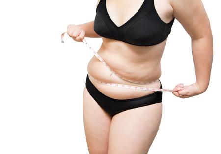 mujer gorda: demostración de la mujer de grasa y apretar apretar la grasa corporal mediante cinta métrica o cinta línea de ropa interior llevaba sujetador negro sobre blanco aislado