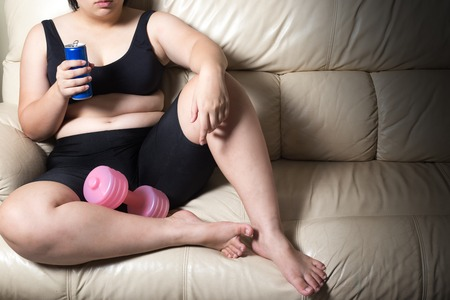 fat woman tired give up exercise concept and soft drink in hand drop dumbbell sitting on sofa