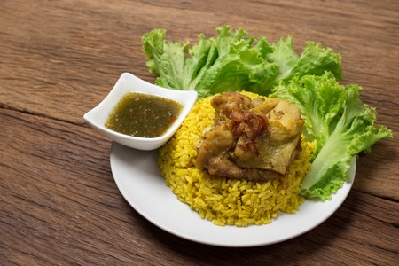 Thai chicken biryani (Khao Mok Gai) or Yellow curry rice Thai Food Style on wood background Imagens