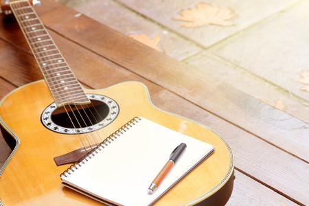 Akoestische gitaar met notitieboekje en pen op houten achtergrond