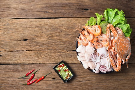seafood mixed with spicy sauce on wooden background crab shrimp squid and fish in plate Imagens
